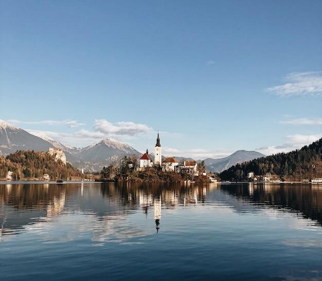 Antigo castelo cercado por um cenário montanhoso, refletindo no lago