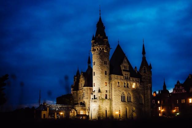 Antigo castelo polonês na vila de moszna nas luzes noturnas