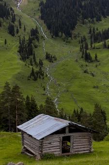 Antigo celeiro de madeira cercado por florestas e rochas com o rio