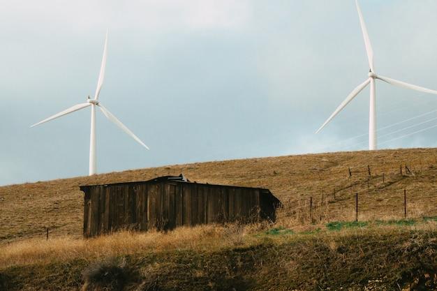 Antigo celeiro de madeira em um campo com dois moinhos de vento sob o sol durante o dia
