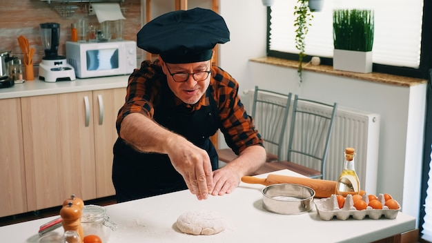 Antigo chef profissional polvilhando farinha na massa na cozinha de casa. padeiro sênior idoso com bonete e peneiramento uniforme, peneirar, espalhar ingredientes refogados manualmente, assar pizzas e pães caseiros.