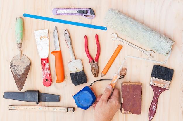 Antigo conjunto de ferramentas de mão de construção com mão de trabalhador sobre fundo branco de madeira