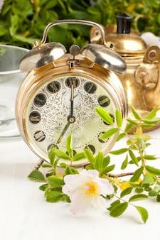 Antigo despertador e bule com flores