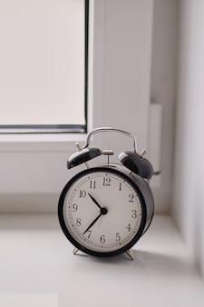 Antigo despertador mecânico preto e branco relógio está no peitoril da janela