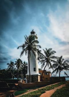 Antigo farol na praia com palmeiras