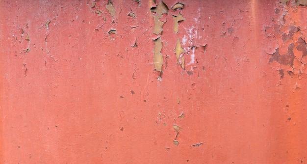 Antigo fundo de metal pintado enferrujado. textura de pintura descascada vermelha.