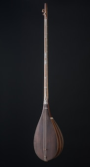 Antigo instrumento musical de cordas asiático em fundo preto com luz de fundo
