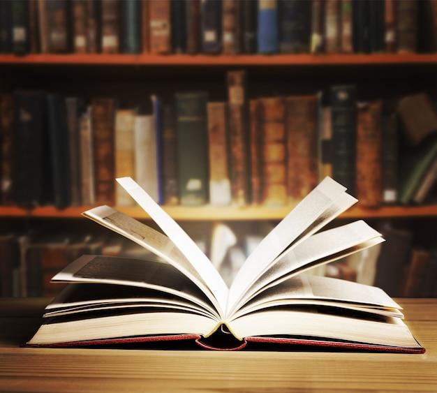 Antigo livro aberto sobre um fundo de estante.