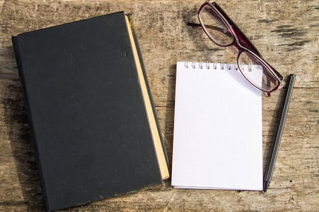Antigo livro fechado, óculos, bloco de notas e caneta em fundo de madeira