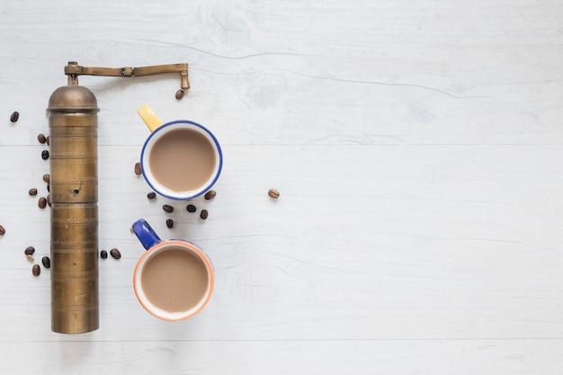 Antigo moedor de café e grãos de café com café quente em pano de fundo de madeira