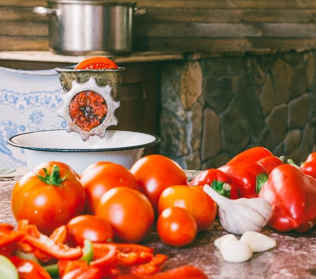 Antigo moedor manual vintage e fatias de tomate fresco, pimentão vermelho e alho em cima da mesa