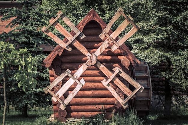 Antigo moinho de vento de madeira na zona rural com árvores verdes