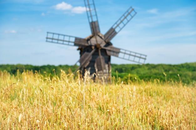 Antigo moinho no campo de trigo amarelo com céu azul