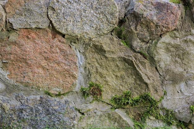 Antigo muro de contenção de paralelepípedos de granito lascado com musgo crescendo nas costuras. vista de perto