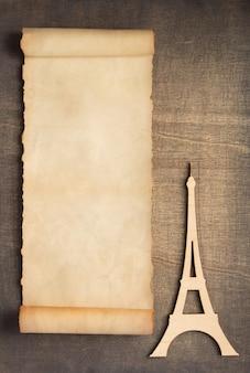 Antigo pergaminho de papel envelhecido retrô e brinquedo da torre eiffel em fundo de madeira