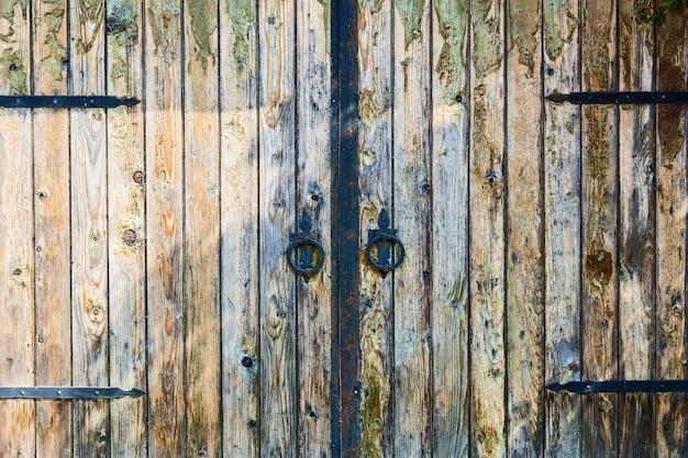 Antigo portão de madeira com maçanetas redondas forjadas e dobradiças forjadas penduradas