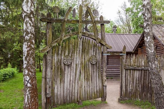 Antigo portão de madeira com musgo verde e sobreposições esculpidas em forma de sol