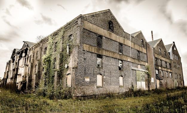 Antigo prédio de pedra abandonado com janelas quebradas sob o céu escuro e nublado