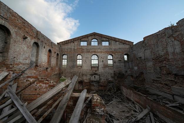 Antigo prédio de tijolos em ruínas sem telhado, sob um céu azul aberto.
