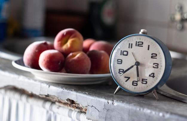 Antigo relógio azul na frente de um prato de ameixas, marcando o tempo para um lanche