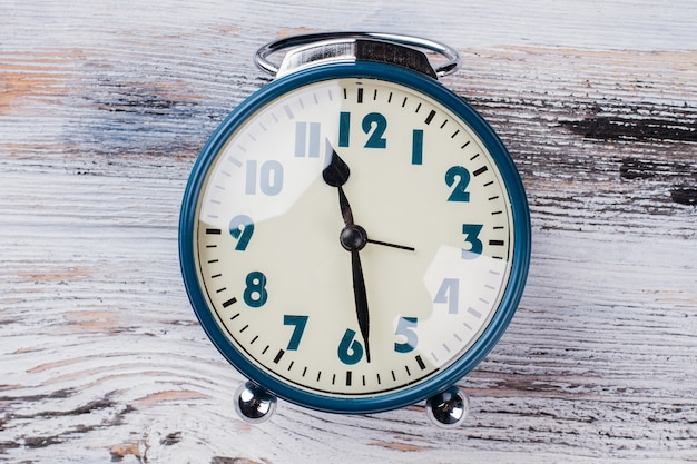 Antigo relógio vintage em fundo branco de madeira. feche o despertador retro azul. seis da tarde ou da manhã.