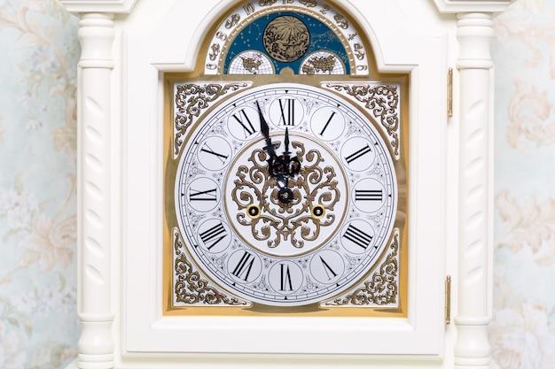 Antigo relógio vintage mostra cinco minutos para doze.