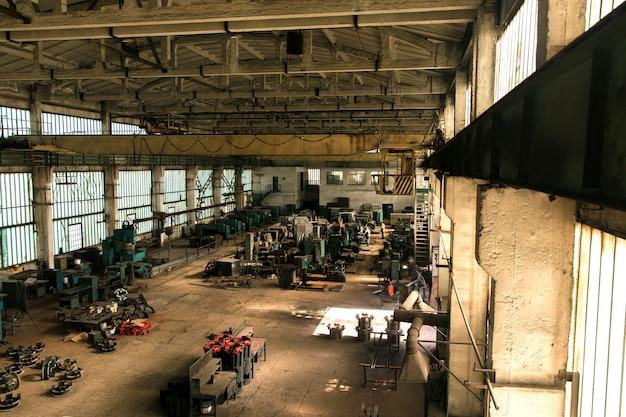 Antigo salão da fábrica com equipamentos e máquinas e trabalhadores