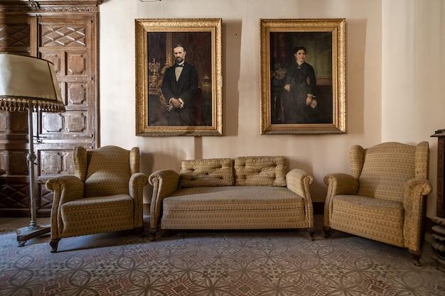 Antigo salão de uma mansão com grandes pinturas nas paredes