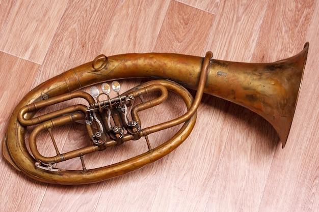 Antigo saxhorn enferrujado em fundo de madeira.