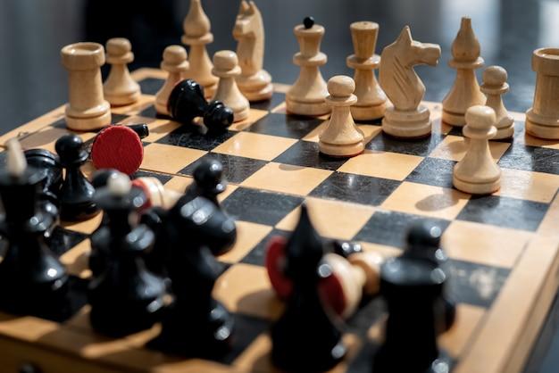 Antigo tabuleiro de xadrez de madeira com um conjunto de peças pretas e brancas em uma posição caótica durante o jogo