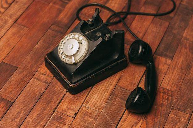 Antigo telefone preto no chão, vintage