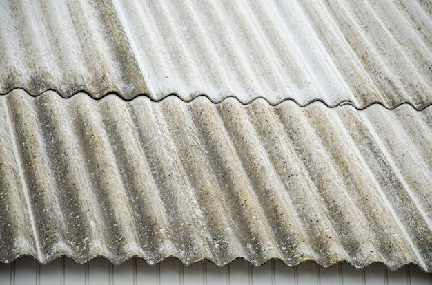 Antigo telhado de ardósia ondulado. textura de ardósia velha. telhado de galpão coberto com velhas placas de amianto.