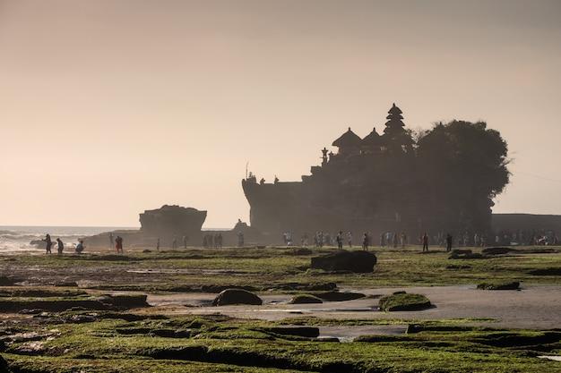 Antigo templo de tanah lot com turistas sonhadores no litoral