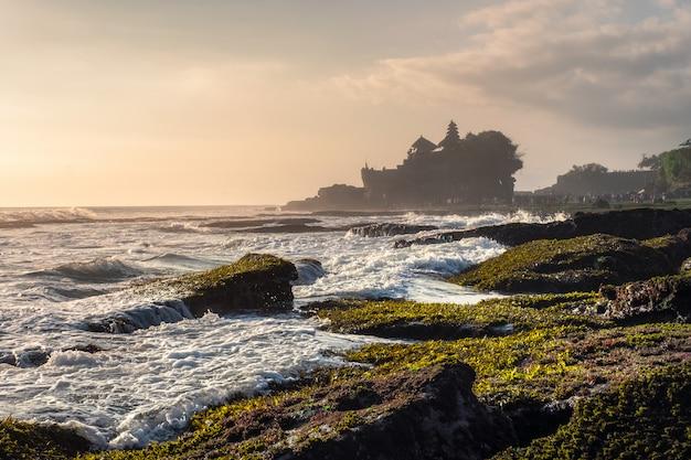 Antigo templo de tanah lot na montanha rochosa no litoral