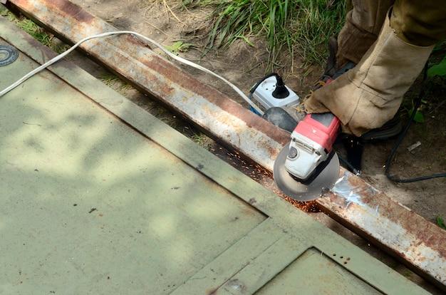 Antigo trabalhador manual em luvas de proteção, corte a porta de metal com moedor