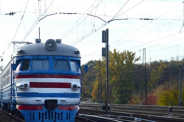 Antigo trem elétrico soviético com design desatualizado, movendo-se por via férrea