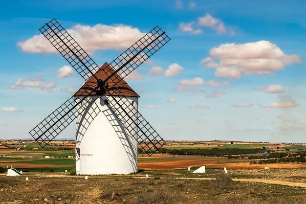 Antigos moinhos de vento brancos, feitos de pedra, no campo com céu azul e nuvens brancas. la mancha, castilla, espanha. europa.
