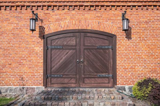 Antigos portões de madeira com aros de ferro, degraus de pedra de granito e lâmpadas nas laterais na parede de tijolo vermelho, close-up