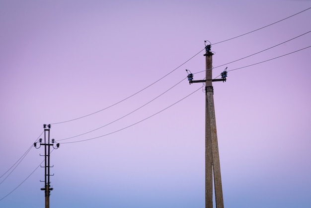 Antigos postes de eletricidade de concreto no crepúsculo.