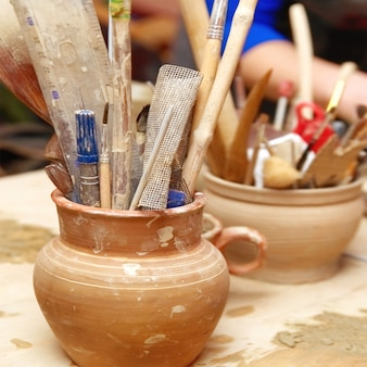 Antigos potes de barro feitos à mão com lápis e outras coisas na mesa