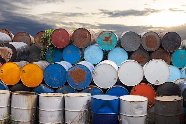 Antigos tanques de metal químico ao pôr do sol, tambores de aço com óleo sujo, meio ambiente, descarte de produtos químicos