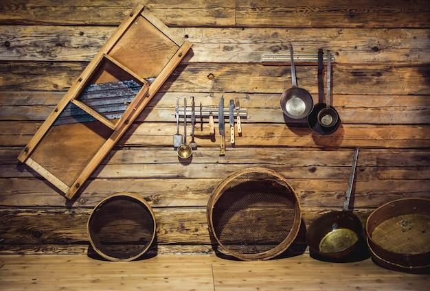 Antigos utensílios tradicionais pendurados na parede de madeira da cozinha