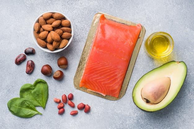 Antioxidantes de alimentos saudáveis: peixe e abacate, nozes em um fundo cinza concreto.