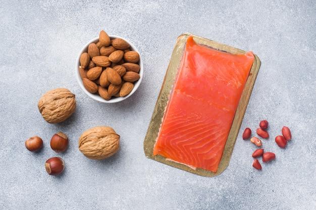 Antioxidantes de produtos alimentares saudáveis: peixes e diferentes tipos de nozes em um fundo cinza de concreto.