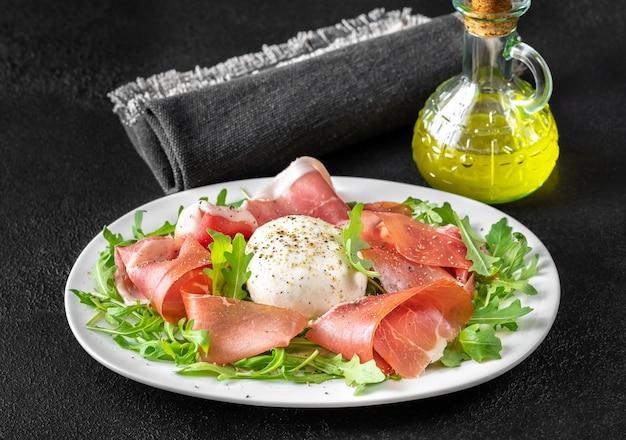 Antipasto com presunto, mussarela e rúcula fresca no prato de servir