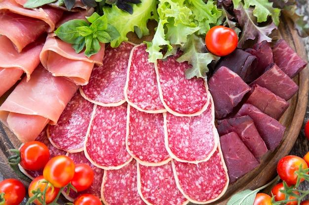 Antipasto com presunto, salame e bresaola. tomate e manjericão. foco seletivo