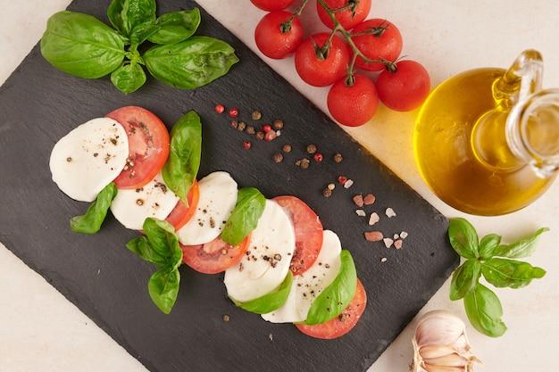 Antipasto de salada italiana fresca chamado caprese com mussarela de búfala, tomate fatiado e manjericão com azeite de oliva. ingredientes para salada caprese vegetariana. comida italiana. vista do topo. estilo rústico.