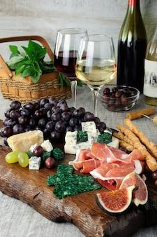 Antipasto em uma tábua de madeira com presunto e diferentes tipos de uvas de queijo e figo