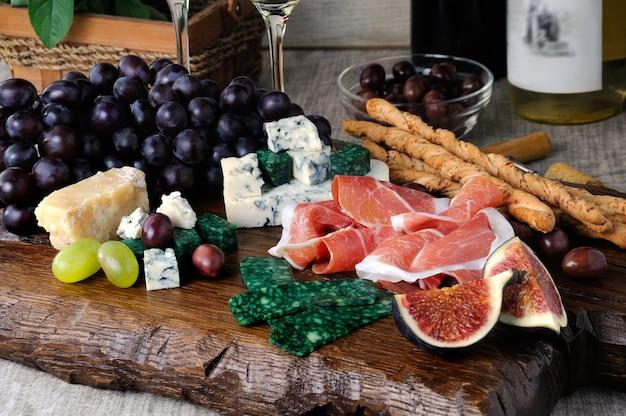 Antipasto em uma tábua de madeira com presunto e diferentes tipos de uvas de queijo e figos em uma mesa