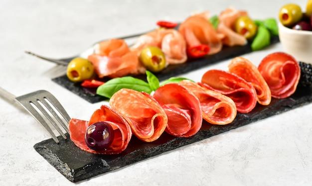 Antipasto no restaurante italiano com prosciutto e salame, azeitonas. servido em pratos de pedra preta.
